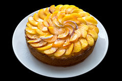 Peach cake. On white plate. Black isolate background Royalty Free Stock Image