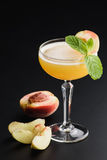 Peach champagne cocktail `bellini` on dark background with mint stock image