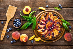 Peach cheese cake or pie with fresh blueberry on wooden rustic background, top view Royalty Free Stock Images