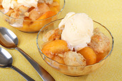 Peach Cobbler Dessert. Two bowls of peach cobbler with ice cream on top royalty free stock images