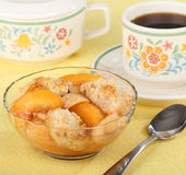 Peach Cobbler Dessert. Peach cobbler in a bowl with a cup of coffee royalty free stock photo