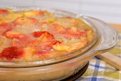 Peach Cobbler Dessert Dish. In a glass dish sitting on a plaid tablecloth Stock Photography