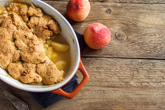 Peach cobbler. Homemade peach cobbler (crumble) in baking dish over rustic wooden background stock image