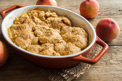 Peach cobbler. Homemade peach cobbler (crumble) in baking dish over rustic wooden background royalty free stock photo