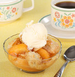 Peach Cobbler and Ice Cream. Bowl of peach cobbler with a scoop of ice cream and a cup of coffee stock images