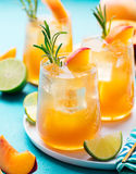 Peach cocktail, fizz, ice tea with fresh rosemary and lime. Blue background. Stock Image