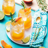 Peach cocktail, fizz, ice tea with fresh rosemary and lime. Blue background. Royalty Free Stock Photography