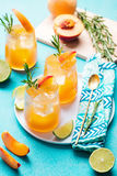 Peach cocktail, fizz, ice tea with fresh rosemary and lime. Blue background. Royalty Free Stock Photos