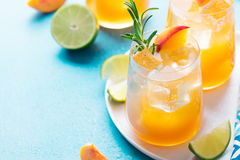 Peach cocktail, fizz, ice tea with fresh rosemary and lime. Blue background. Copy space. Royalty Free Stock Photo