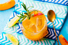 Peach cocktail, fizz, ice tea with fresh rosemary and lime. Blue background. Top view. Stock Photography
