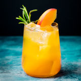 Peach cocktail, fizz with rosemary on blue stone background. Stock Photography