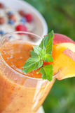 Peach cocktail with mint leaves. Peach cocktail in the garden in hot summer, sunny day Royalty Free Stock Image