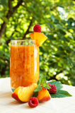 Peach coctail with raspberries. Peach cocktail in the garden in hot summer, sunny day with raspberries Royalty Free Stock Photos