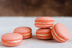 Peach color macaroons. On rustic background. Shallow focus stock photography