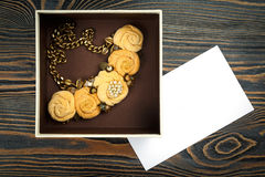 Peach-colored handmade necklace putted in a box and a letter of congratulations are lying on wooden background Stock Photos