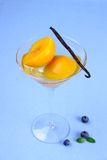 Peach compote in glass bowl with blueberries and vanilla Royalty Free Stock Photos
