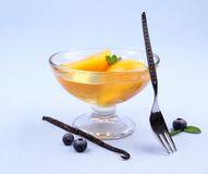Peach compote in glass bowl with fork, blueberries and vanilla Stock Photos