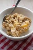 Peach Crisp. Homemade peach crisp in a white bowl and spoon Stock Photo