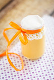 Peach curd. In a jar with orange ribbon. On fabric with violet dots Stock Photography