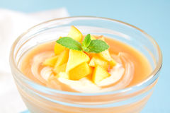 Peach dessert. (mousse) with yogurt and mint on blue background royalty free stock image
