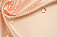 Peach draped background. Peach silk background with drapery in the corner and drops Royalty Free Stock Images