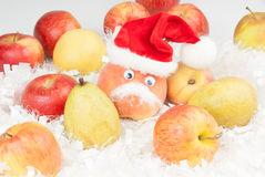 Peach with eyes and Santa Clause hat and mustache. On the white like a snow decor is several fruits and one red color peach with Santa Clause hat on the top of Royalty Free Stock Photos