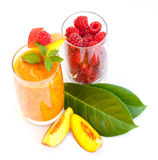 Peach fresh with raspberries. Two glasses one with peach fresh juice other with delicious raspberries and two green leaves for decoration Royalty Free Stock Photography