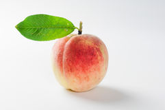 Peach with green leaf. Fresh peach on white background with green leaf Stock Image