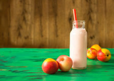 Peach fruit smoothie in glass bottle on green wooden table. Healthy lifestyle, selective focus Stock Photo