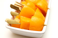 Peach fruits on skewers in white cup Royalty Free Stock Image