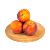 Peach fruits on wooden board Stock Photos