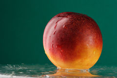Peach on the glass. Table over green background stock photography