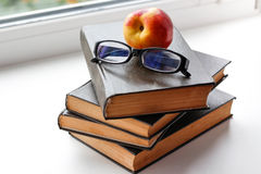 Peach and glasses lies on four big black books. Closeup Royalty Free Stock Photography