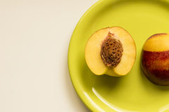 Peach on a green plate. Ideal for wallpapers. Could be useful in presentations, web and printing design Stock Photography
