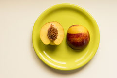 Peach on green plate. Ideal for wallpapers. Could be useful in presentations, web and printing design Stock Photo