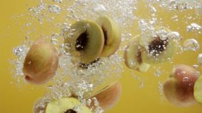 Peach halves falling in water in slow motion. stock footage