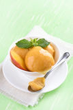 Peach ice cream. In bowl on green wooden background Stock Photos