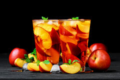 Peach ice tea. In a glass with mint on a black wooden tableselective focus royalty free stock photos