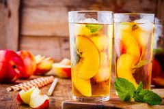 Peach ice tea in a glass with mint Stock Image