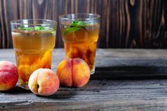 Peach ice tea in a glass with mint on wooden table Royalty Free Stock Photo