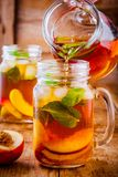 Peach ice tea in mason jar with mint Stock Images
