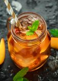 Peach Ice tea with mint in glass jar, on rustic black background. summer fruit cold drinks royalty free stock images