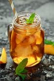 Peach Ice tea with mint in glass jar, on rustic black background. summer fruit cold drinks stock photo
