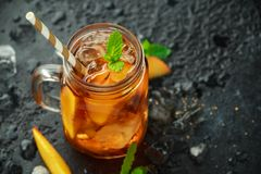 Peach Ice tea with mint in glass jar, on rustic black background. summer fruit cold drinks.  royalty free stock image