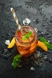 Peach Ice tea with mint in glass jar, on rustic black background. summer fruit cold drinks royalty free stock photography
