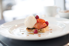 Peach and icecream dessert. Peaches served on a toasted pastry with iceacream and raspberries Royalty Free Stock Images