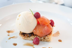Peach and icecream dessert. Peaches served on a toasted pastry with iceacream and raspberries Royalty Free Stock Photo
