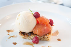Peach and icecream dessert. Peaches served on a toasted pastry with iceacream and raspberries Royalty Free Stock Photos