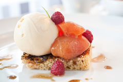 Peach and icecream dessert. Peaches served on a toasted pastry with iceacream and raspberries Stock Images