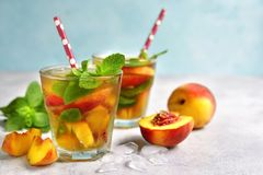 Peach iced tea with mint. In a glass on a light background royalty free stock photography